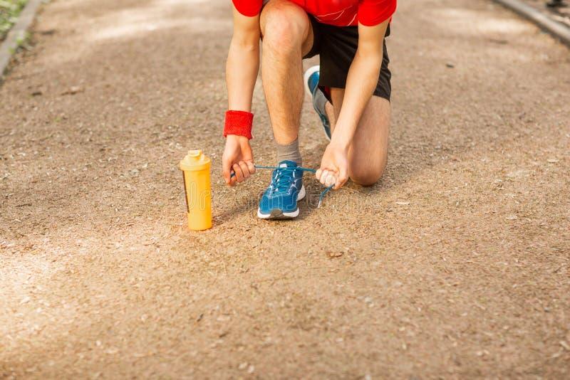 Giovane corridore bello che lega i laccetti sul parco della pista in primavera Vicino lui ? una termocoppia arancio immagine stock