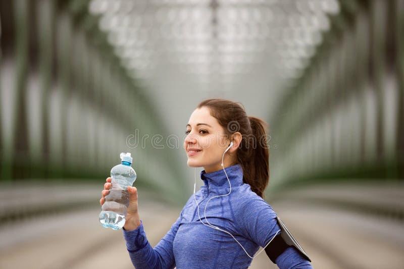 Giovane corridore che riposa, acqua potabile sul ponte d'acciaio verde immagine stock