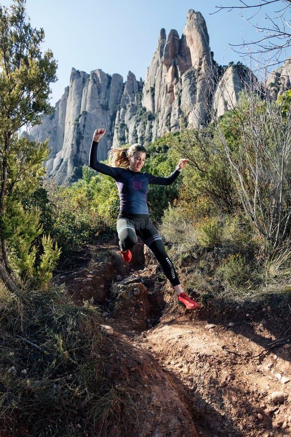 Giovane corridore della traccia della donna di forma fisica che corre e che salta sulla montagna rocciosa fotografia stock