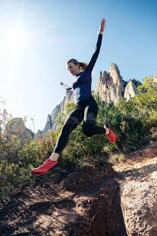 Giovane corridore della traccia della donna di forma fisica che corre e che salta sulla montagna rocciosa immagini stock libere da diritti