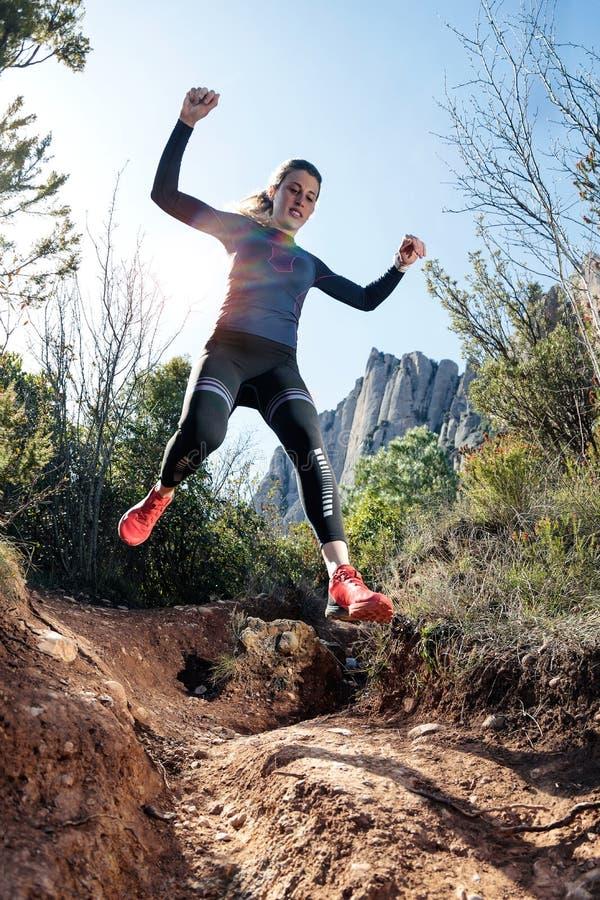 Giovane corridore della traccia della donna di forma fisica che corre e che salta sulla montagna rocciosa immagini stock