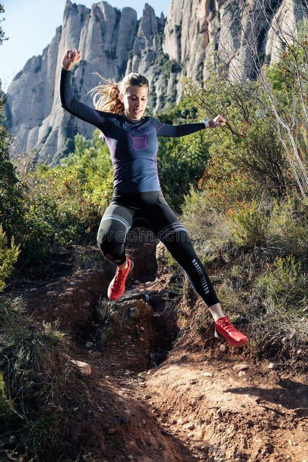 Giovane corridore della traccia della donna di forma fisica che corre e che salta sulla montagna rocciosa immagine stock libera da diritti