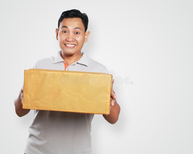 Giovane corriere asiatico divertente Guy Giving Package Box immagine stock