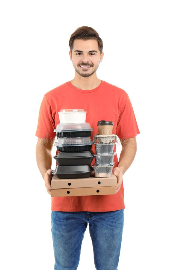Giovane corriere con i contenitori, i contenitori e le bevande di pizza su fondo bianco immagini stock libere da diritti
