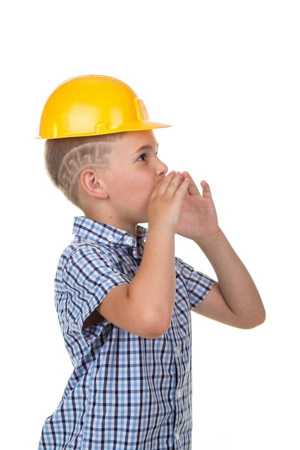 Giovane costruttore bello nel casco a quadretti blu della costruzione e della camicia che grida qualcosa, costruendo concetto immagine stock