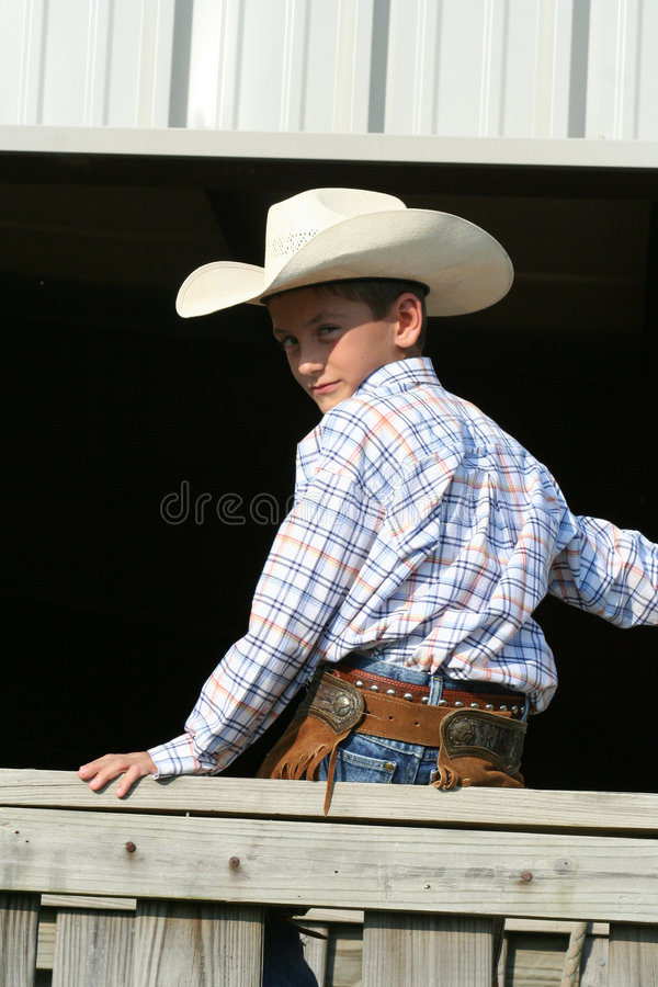 Giovane cowboy sulla rete fissa fotografia stock