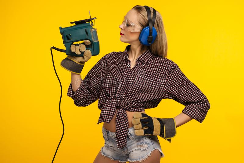 Giovane craftswoman con un puzzle davanti a fondo giallo immagine stock