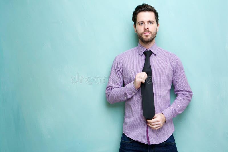 Giovane cravatta della tenuta dell'uomo d'affari immagine stock