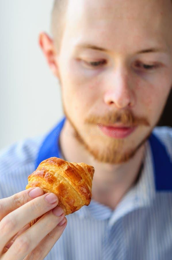 Giovane croissant mangiatore di uomini fotografia stock libera da diritti