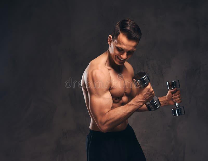 Giovane culturista senza camicia con l'ente muscolare che fa esercizio con le teste di legno su fondo scuro immagini stock