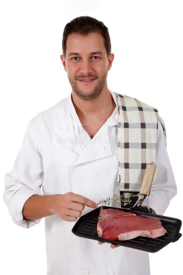 Giovane cuoco maschio caucasico attraente, bistecca di bistecca con l'osso immagini stock