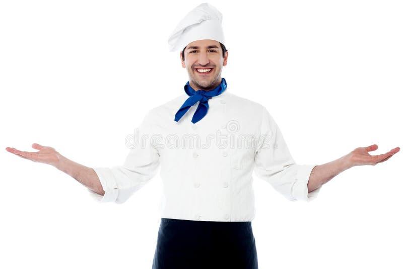 Giovane cuoco unico astuto che accoglie favorevolmente gli ospiti immagine stock