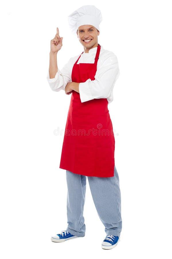 Giovane cuoco unico astuto che indica il dito indice verso l'alto immagini stock