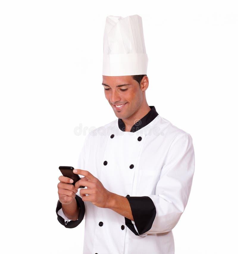 Giovane cuoco unico bello che legge un messaggio fotografia stock