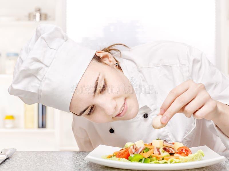 Giovane cuoco unico che decora insalata squisita immagine stock