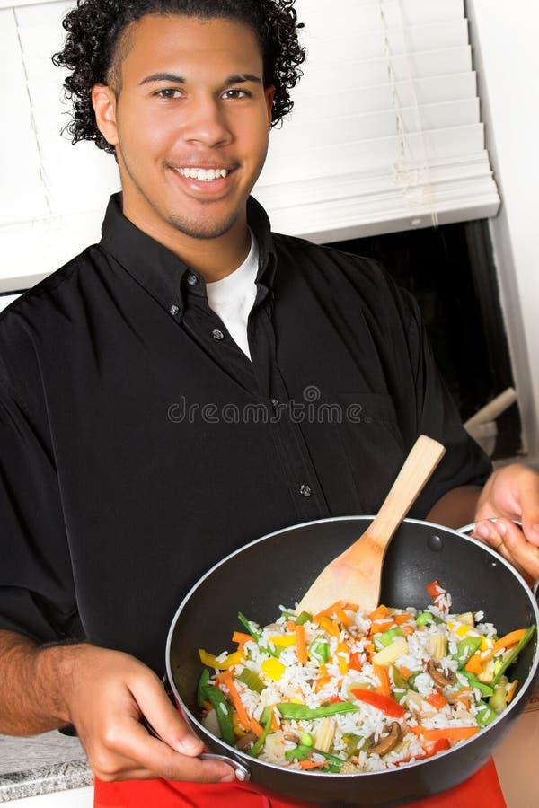 Giovane cuoco unico con il wok fotografie stock libere da diritti