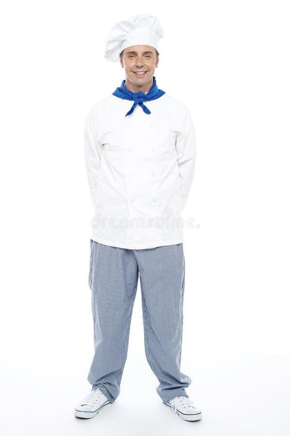 Giovane cuoco unico maschio sorridente astuto che propone con indifferenza fotografie stock libere da diritti