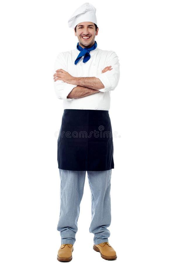 Giovane cuoco unico maschio sorridente con le armi attraversate immagini stock libere da diritti