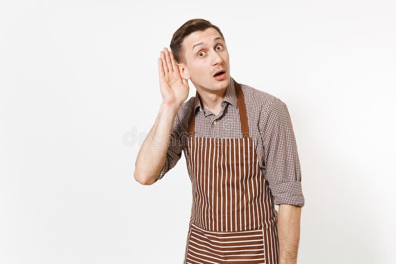 Giovane cuoco unico o cameriere interessato dell'uomo di divertimento in grembiule marrone a strisce, camicia ascoltare di nascos fotografia stock libera da diritti