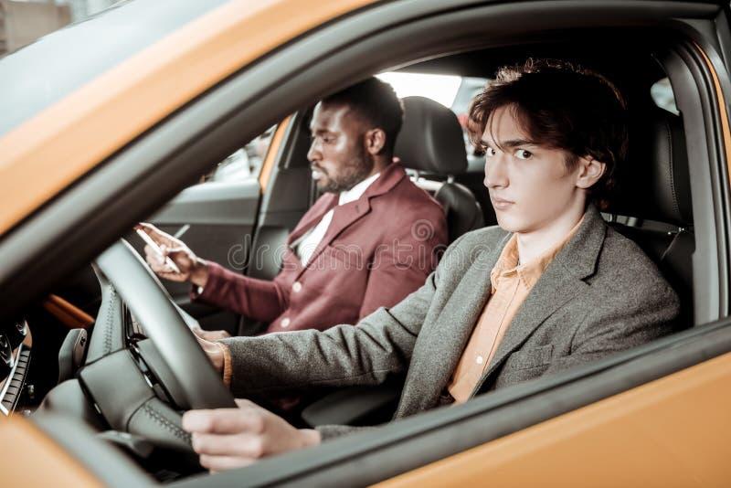 Giovane dagli occhi scuri che ritiene nervoso mentre guidando per la prima volta immagine stock libera da diritti
