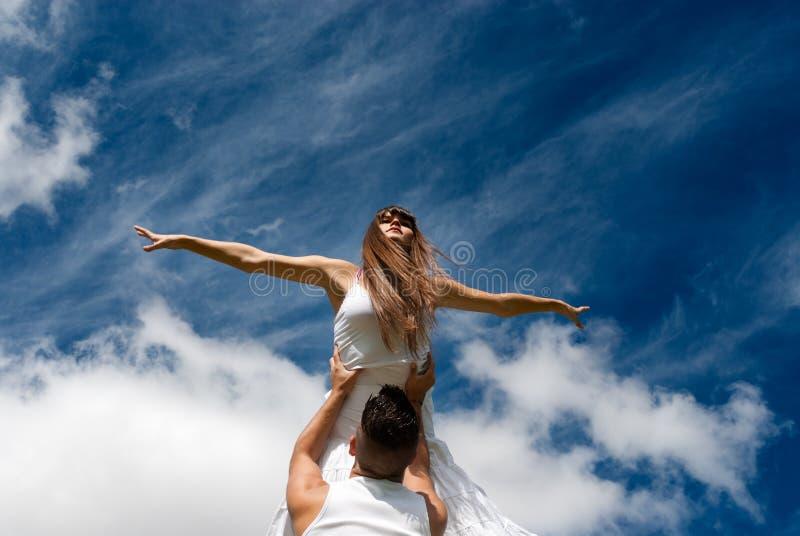 Giovane dancing delle coppie sulla priorità bassa del cielo, libertà immagini stock