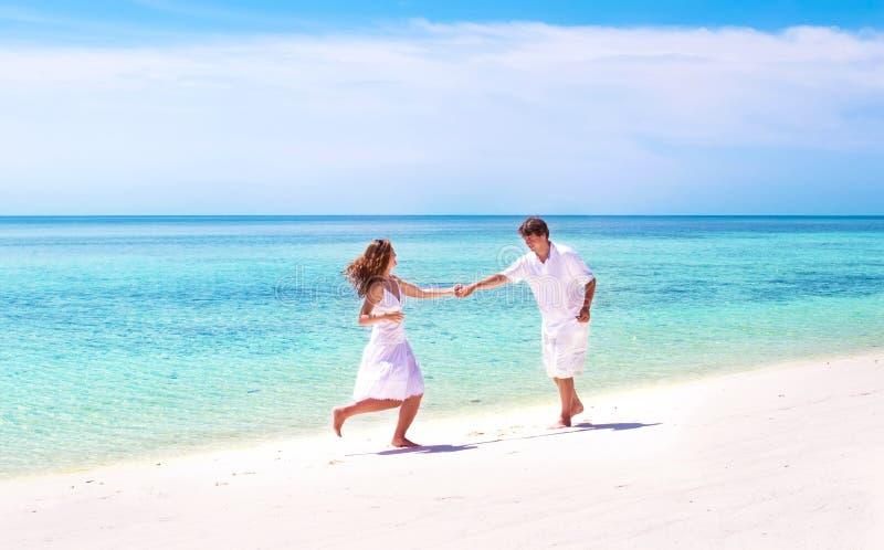 Giovane dancing delle coppie sulla spiaggia dell'isola tropicale fotografia stock libera da diritti