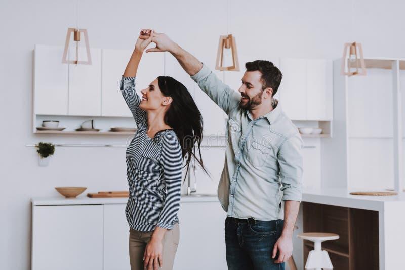 Giovane dancing felice delle coppie nella cucina moderna fotografia stock libera da diritti