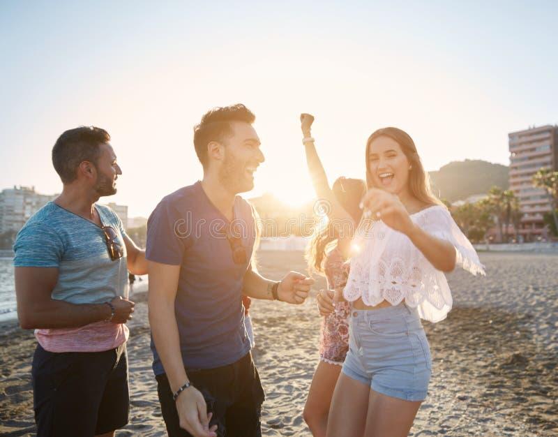 Giovane dancing grazioso della donna con gli amici sulla spiaggia immagine stock