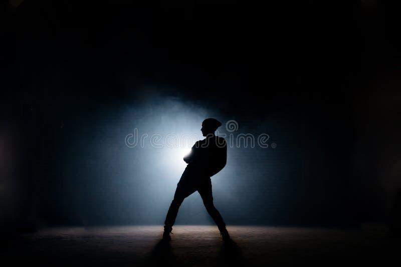 Giovane dancing maschio sulla fase scura prima prestazione Corpo piegato immagini stock