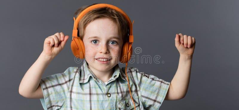 Giovane dancing sorridente del ragazzo, ascoltante la musica sulle cuffie fotografia stock