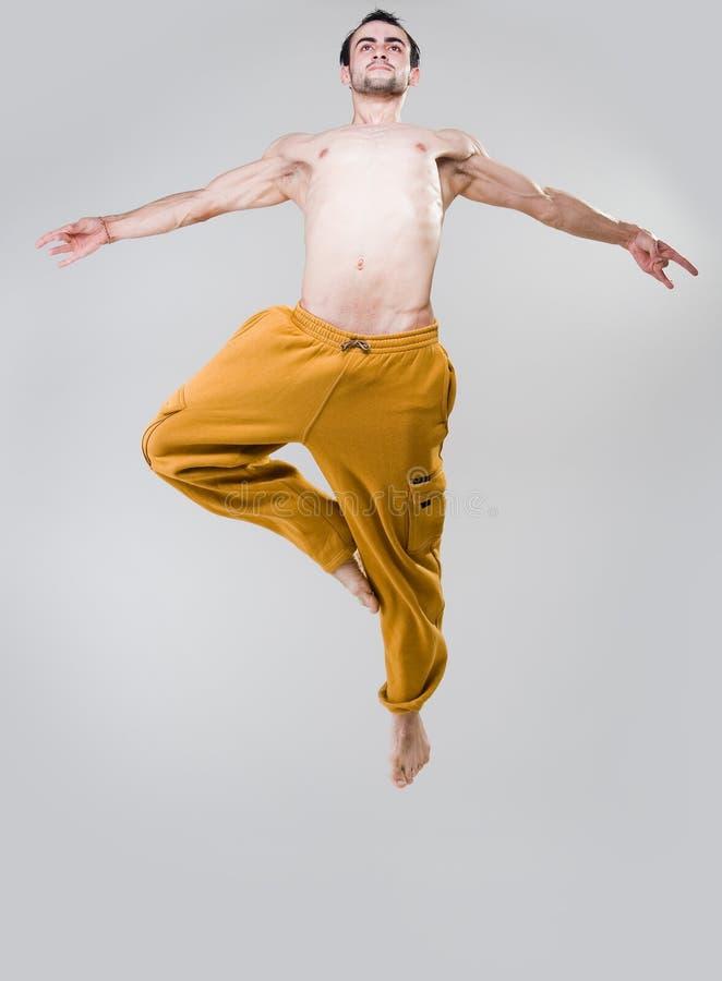 Giovane danzatore che salta sopra la priorità bassa grigia fotografia stock