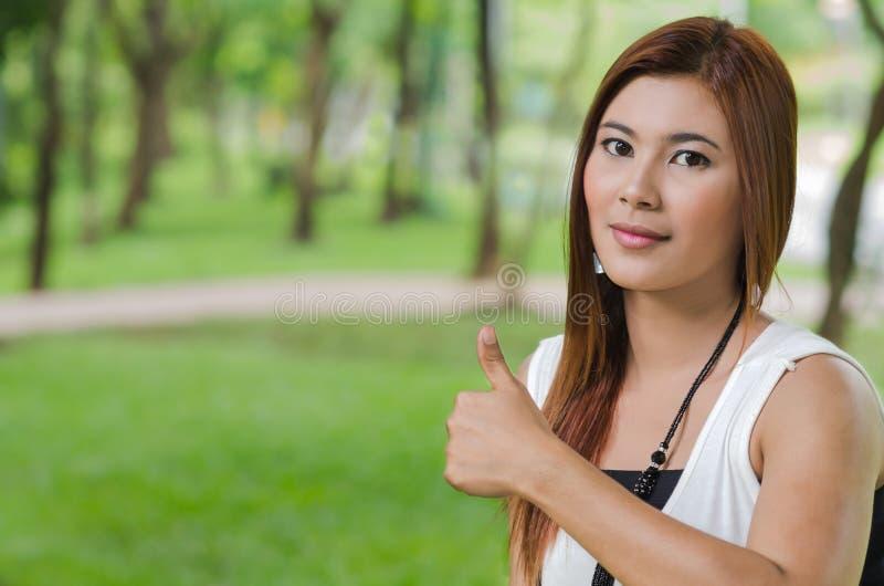 Giovane dare asiatico attraente della donna pollici su immagini stock libere da diritti
