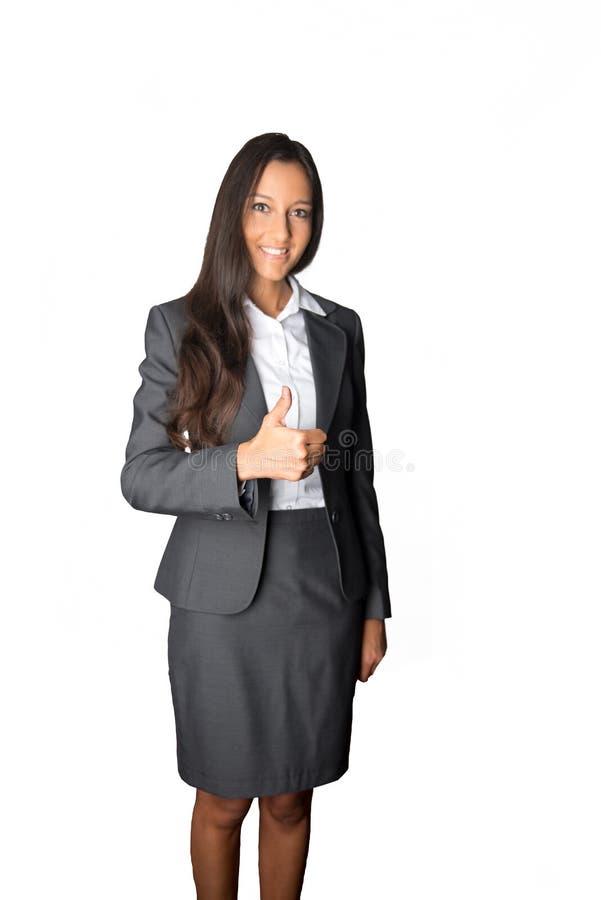 Giovane dare astuto della donna di affari pollici su fotografia stock