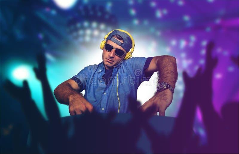 Giovane deejay felice e fresco che gioca musica all'evento del partito in night-club che mescola le canzoni techne sul laser e su fotografia stock