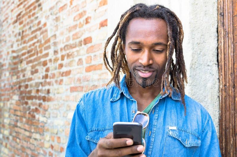 Giovane dei pantaloni a vita bassa afroamericani che per mezzo dello Smart Phone mobile immagine stock