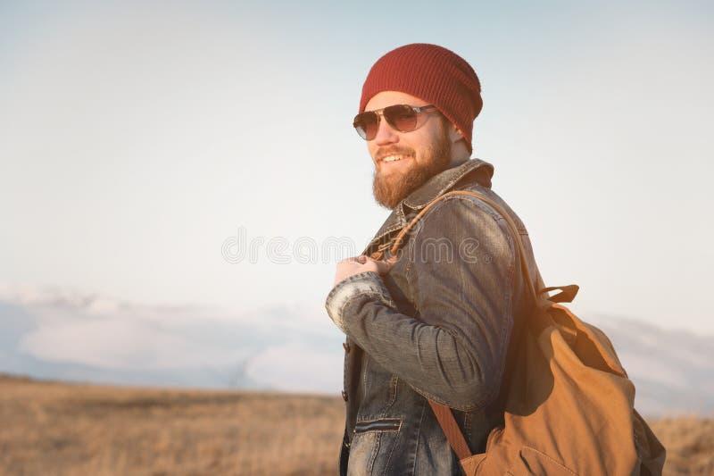 Giovane dei pantaloni a vita bassa con gli occhiali da sole d'uso dei baffi e della barba che posano contro lo sfondo delle monta immagine stock libera da diritti