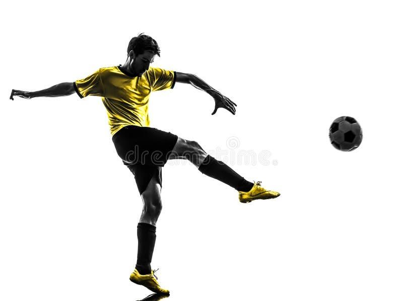 Giovane del giocatore di football americano brasiliano di calcio che dà dei calci alla siluetta fotografie stock