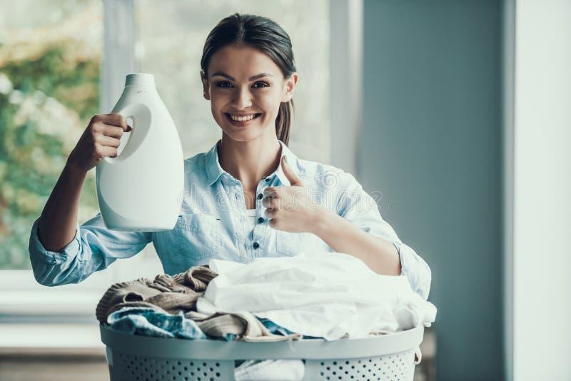 Giovane detersivo di lavanderia sorridente della tenuta della donna immagini stock libere da diritti