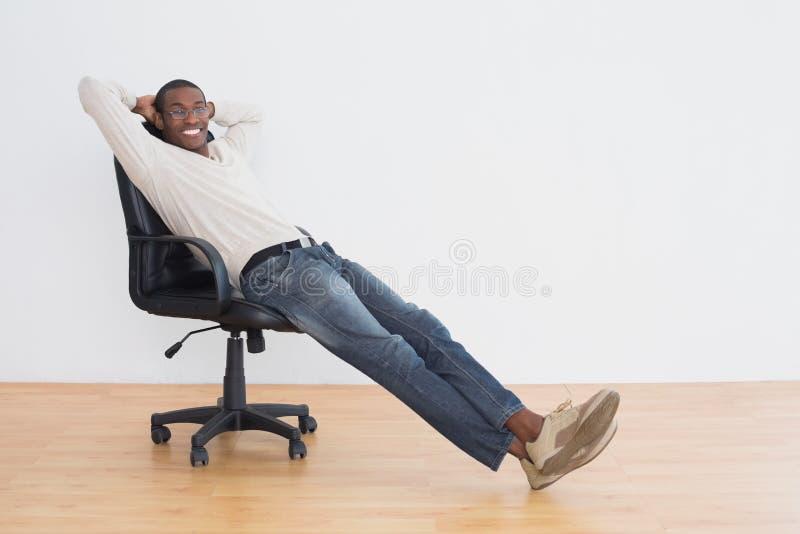Giovane di afro casuale che si siede sulla sedia dell'ufficio in una stanza vuota fotografia stock