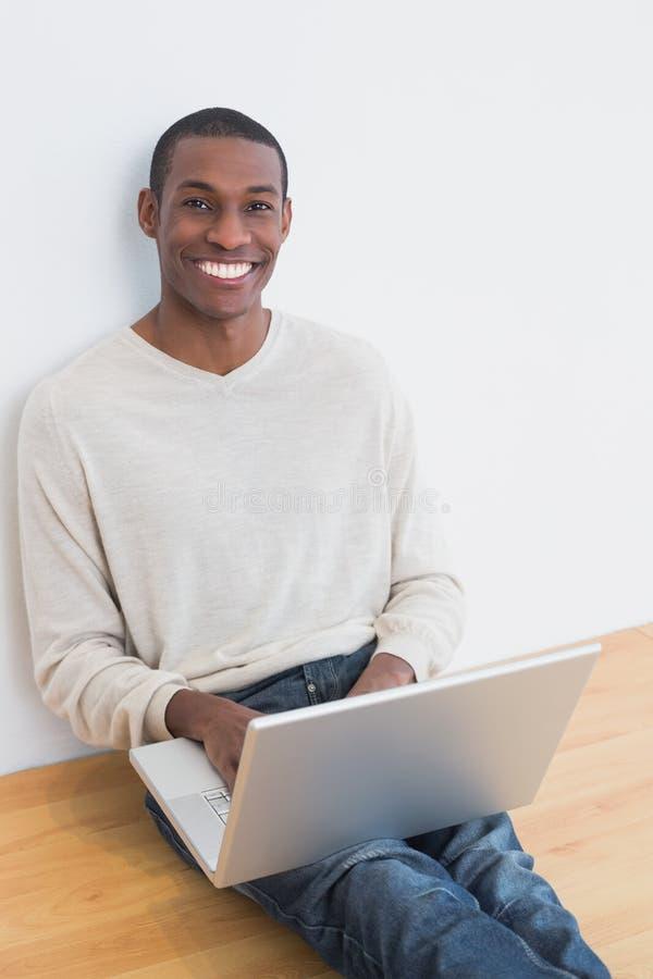 Giovane di afro casuale felice che per mezzo del computer portatile sul pavimento fotografia stock libera da diritti