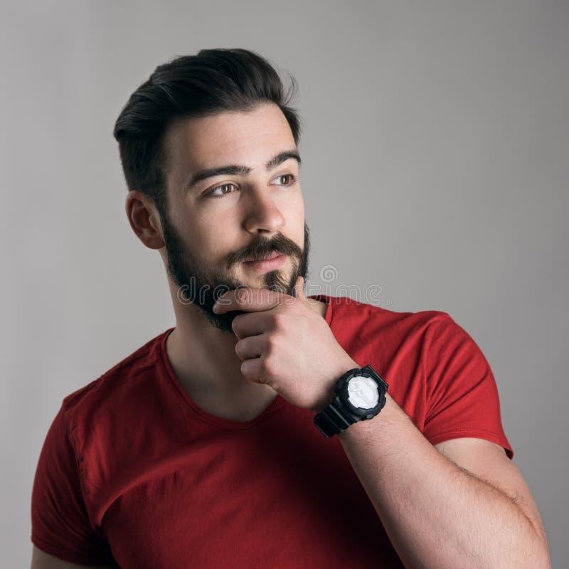 Giovane di pensiero fresco con la mano sul mento che tocca suo distogliere lo sguardo della barba immagine stock