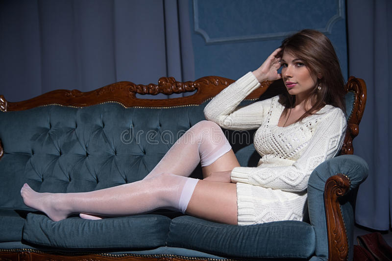 Giovane disposizione dei posti a sedere castana attraente della donna su un sofà immagini stock