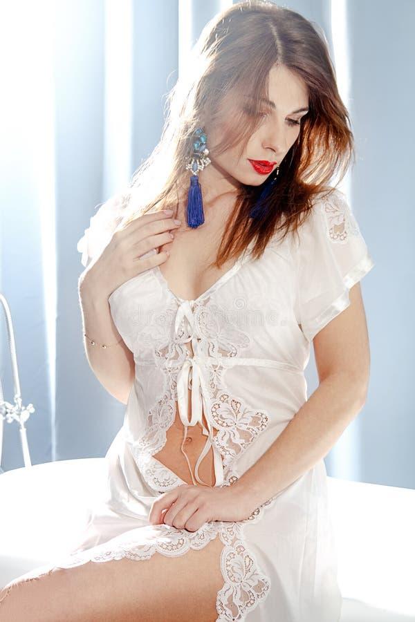 Giovane disposizione dei posti a sedere castana attraente della donna sul bordo del bagno fotografia stock libera da diritti