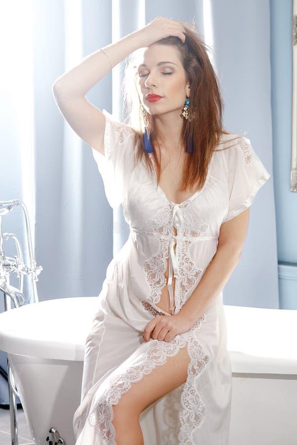 Giovane disposizione dei posti a sedere castana attraente della donna sul bordo del bagno immagine stock