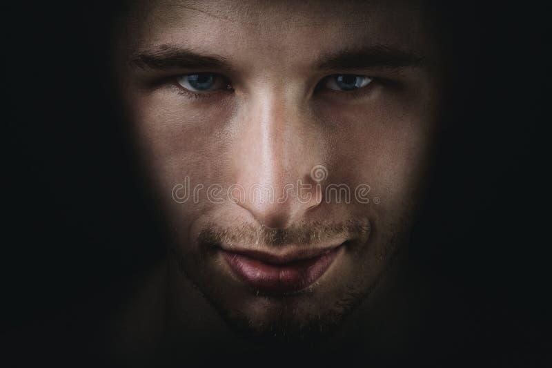 Giovane dissolvenza adulta scura del ritratto dell'uomo nel nero fotografia stock