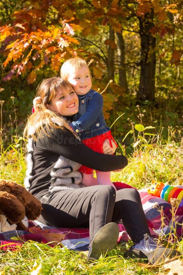 Giovane divertimento di risata della figlia e della madre ai precedenti degli alberi di autunno nel legno fotografie stock