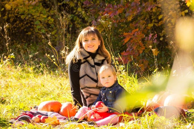 Giovane divertimento di risata della figlia e della madre ai precedenti degli alberi di autunno nel legno fotografie stock libere da diritti