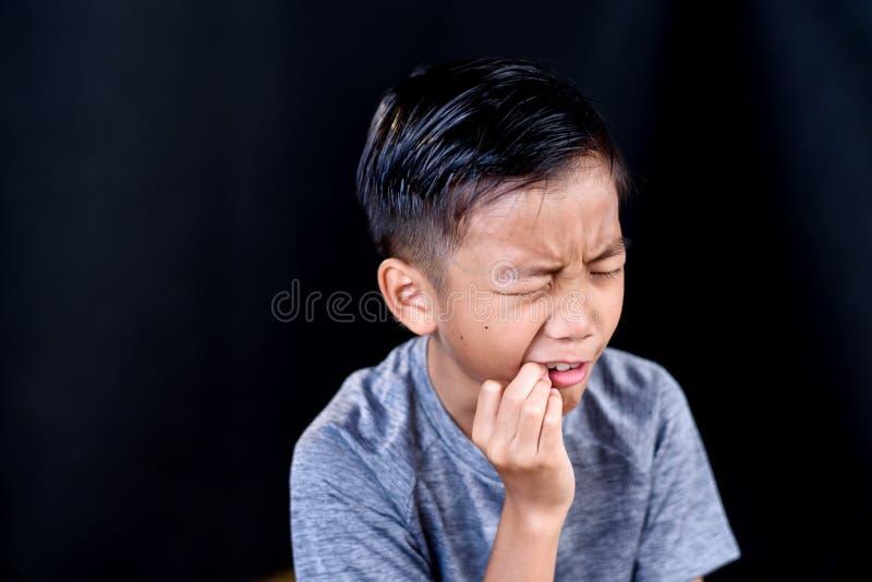 Giovane dolore asiatico di tatto del ragazzo fotografie stock libere da diritti
