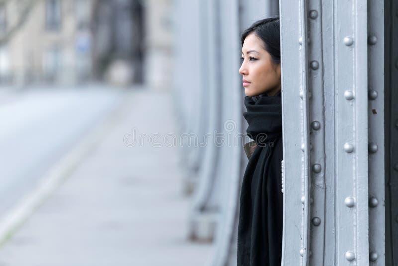 Giovane donna abbastanza asiatica che guarda lateralmente nella via fotografie stock