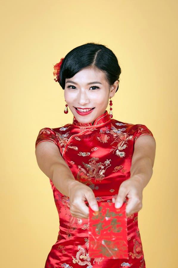 Giovane donna abbastanza cinese che tiene tasca rossa per il nuovo anno cinese felice immagini stock libere da diritti